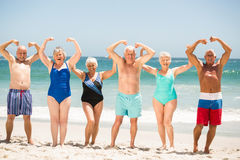 Aînés posant avec des muscles à la plage Photographie stock