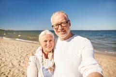 Aînés prenant la photo avec le bâton de selfie sur la plage Images libres de droits