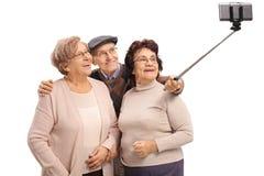 Aînés prenant un selfie avec un bâton Image stock
