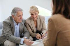 Aînés rencontrant le contrat de lecture d'agent immobilier Photo libre de droits