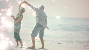 Aînés retirés heureux dansant sur la plage avec l'animation de coeurs pour le Saint Valentin banque de vidéos