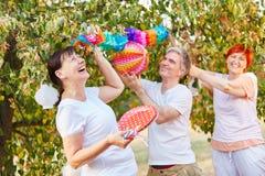Aînés riant et ayant l'amusement tout en décorant pour une partie Photo libre de droits