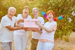 Aînés riant et souriant avec un cadeau d'anniversaire Images stock
