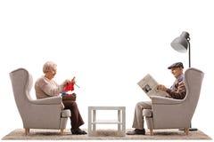 Aînés s'asseyant dans des fauteuils avec un du tricotage ils et de l'o Images stock
