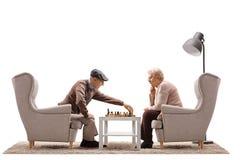 Aînés s'asseyant dans des fauteuils et jouant des échecs Images stock