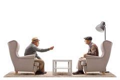 Aînés s'asseyant les fauteuils et en parlant Photo stock