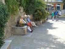Aînés s'asseyant sur le banc abrité du soleil chaud Image libre de droits