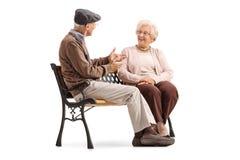 Aînés s'asseyant sur un banc et ayant une conversation Image stock