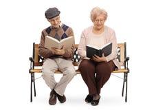 Aînés s'asseyant sur un banc et des livres de lecture Image libre de droits