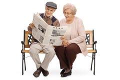 Aînés s'asseyant sur un banc et lisant un journal ensemble Photo stock