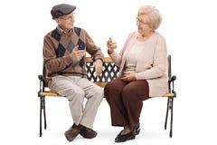 Aînés s'asseyant sur un banc et parlant les uns avec les autres Photos stock