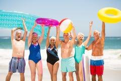 Aînés se tenant dans une rangée à la plage Image stock