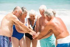Aînés se tenant en cercle à la plage Photographie stock