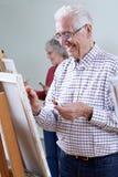 Aînés suivant la classe de peinture ensemble Photo stock