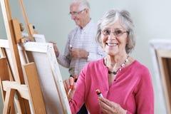 Aînés suivant la classe de peinture ensemble Photo libre de droits