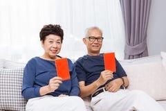 Aînés supérieurs asiatiques chinois donnant l'enveloppe ou le bao rouge de Hong à une plus jeune génération pendant la nouvelle a Photo libre de droits