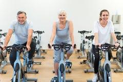 Aînés sur des vélos d'exercice dans la classe de rotation au gymnase image libre de droits