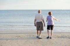 Aînés sur la plage au coucher du soleil Images libres de droits