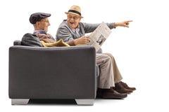 Aînés sur un sofa avec l'un d'entre eux journal de lecture et le transhorizon Photo libre de droits