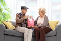 Aînés sur un sofa mettant l'argent dans une tirelire Image stock
