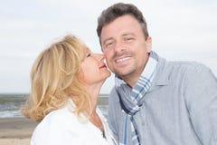 Aînés sur une promenade dans le baiser et l'amour de plage de mer Photographie stock libre de droits