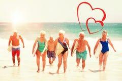 Aînés tenant des planches de surf à la plage Photos libres de droits