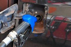 Añada el aceite combustible al coche en el surtidor de gasolina con un dispensador selec Foto de archivo