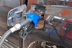 Añada el aceite combustible al coche en el surtidor de gasolina con un dispensador selec Fotos de archivo