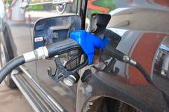 Añada el aceite combustible al coche en el surtidor de gasolina con un dispensador selec Foto de archivo libre de regalías