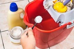 Añada el bicarbonato de sosa al limpiador del piso para la limpieza de la casa Fotografía de archivo libre de regalías
