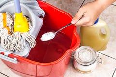 Añada el bicarbonato de sosa al limpiador del piso para la limpieza de la casa Imágenes de archivo libres de regalías
