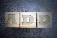 Añada - el texto en los bloques de madera de la textura en fondo gris oscuro Fotos de archivo libres de regalías