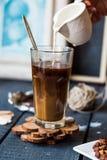 Añada la crema a la taza del café sólo, mano Imágenes de archivo libres de regalías
