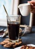 Añada la crema a la taza del café sólo, mano Fotografía de archivo libre de regalías