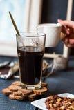 Añada la crema a la taza del café sólo, mano Fotos de archivo