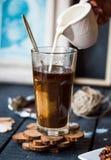 Añada la crema a la taza del café sólo, mano Foto de archivo