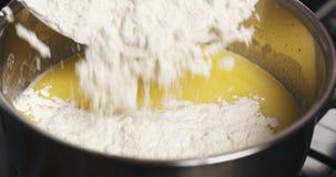 Añada la harina a la mezcla de mantequilla derretida con agua Fotos de archivo