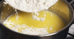 Añada la harina a la mezcla de mantequilla derretida con agua Fotos de archivo libres de regalías