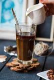 Añada la leche a la taza del café sólo, mano Fotos de archivo