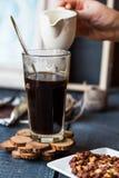 Añada la leche a la taza del café sólo, mano Imagen de archivo libre de regalías