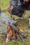 Añada la madera en el fuego, una comida campestre en el bosque Imagen de archivo libre de regalías