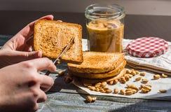 Añada a la mantequilla de cacahuete rubicunda de la tostada, mano, desayuno delicioso Foto de archivo libre de regalías