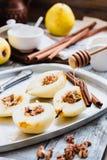 Añada la miel a una pera con las nueces, palillos de canela, cocinando el proce Fotografía de archivo libre de regalías