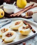Añada la miel a una pera con las nueces, palillos de canela, cocinando el proce Foto de archivo