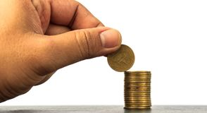 Añada la moneda al top de la pila de la moneda Imagen de archivo libre de regalías