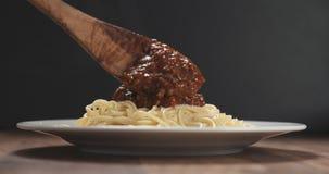 Añada la salsa boloñesa en los espaguetis Imagenes de archivo