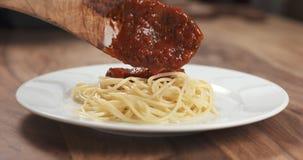 Añada la salsa boloñesa en los espaguetis Foto de archivo libre de regalías