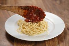 Añada la salsa boloñesa en los espaguetis Fotografía de archivo libre de regalías