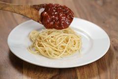 Añada la salsa boloñesa en los espaguetis Foto de archivo