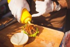 añada la salsa caliente en la hamburguesa Fotografía de archivo